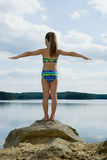 Girl standing on rock by lake Stock Image