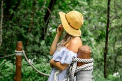 Girl standing on the rope bridge. Beautiful girl in hat, stood on the rope bridge in the rainforest, the concept of leisure and travel Royalty Free Stock Photography