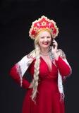 Girl standing in Russian traditional dress with mobile phone. Girl standing in Russian traditional dress. Do selfie. Woman is wearing sarafan and kokoshnik. The stock photo