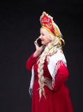 Girl standing in Russian traditional dress with mobile phone Royalty Free Stock Images
