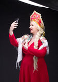 Girl standing in Russian traditional dress with mobile phone Stock Photo