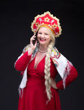Girl standing in Russian traditional dress with mobile phone Royalty Free Stock Image