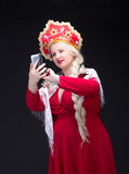 Girl standing in Russian traditional dress with mobile phone Stock Image