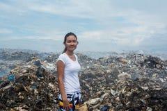 Girl standing sad with trash trash around at garbage dump Royalty Free Stock Photography