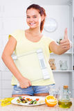 Girl standing with scales on kitchen. Portrait of joyful smiling slim girl standing with scales on kitchen stock image