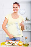 Girl standing with scales on kitchen. Portrait of smiling young slim girl standing with scales on kitchen royalty free stock image