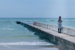 Girl standing on the sea pier in cold season stock photo