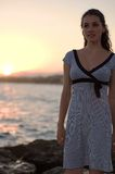 Girl standing on the seabank. A girl standing on the seabank at the sunset stock photography