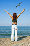 Girl standing at the seashore. The girl standing at the seashore with arms outspread over the head Royalty Free Stock Image