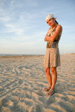 Girl standing on the seashore. Full-length portrait of a woman stanging on the sand on the beach and looking to the camera royalty free stock images