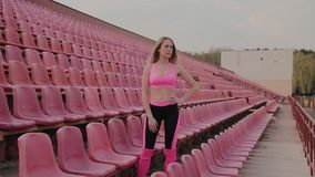 The girl is standing by the seats in the stadium, rest after a run. The girl is standing by the seats in the stadium, rest after a run stock video