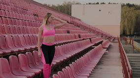 The girl is standing by the seats in the stadium, rest after a run. The girl is standing by the seats in the stadium, rest after a run stock footage