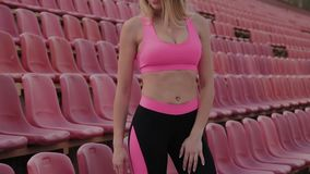 The girl is standing by the seats in the stadium, rest after a run. stock video