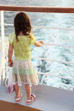 Girl standing on ship deck and looking on waves Stock Photography