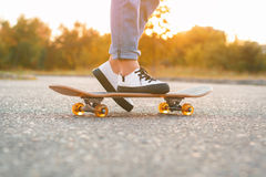 Girl standing on a skateboard. Close up of feet and skateboard. Royalty Free Stock Photo