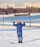 Girl standing on skis with ski poles Stock Photos