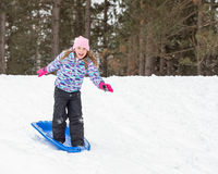Girl Standing on Sled and Snow Surfing Down Hill Royalty Free Stock Photos