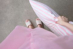 Girl Standing in Sleepwear and Pink Checkered Slippers with Holding Pink Pillow on Floor Background Royalty Free Stock Photos