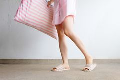 Girl Standing in Sleepwear and Pink Checkered Slippers with Holding Pink Pillow on Floor Background Stock Photography