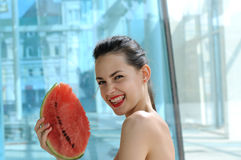 Girl standing with a slice of watermelon and smiling. On a background of blue glass building Stock Photos