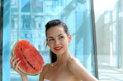 Girl standing with a slice of watermelon and smiling. On a background of blue glass building Stock Images