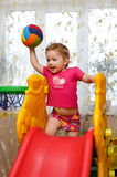 Girl standing on the slide Stock Photos