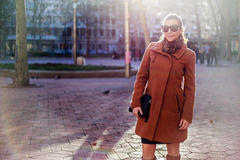 Girl standing and smiling in the city. With sun in the background Royalty Free Stock Images
