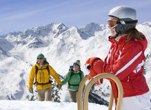 Girl standing in snow with sled, hikers nearby Royalty Free Stock Image