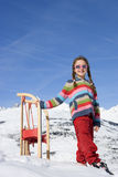 Girl (7-9) standing in snow by sled, wearing sunglasses, smiling, portrait, mountain range in background Royalty Free Stock Images
