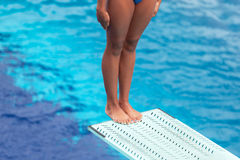 Girl standing on a springboard, preparing to dive into a swimming pool Stock Photography