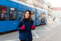 Girl standing in station with tram passing by Stock Image