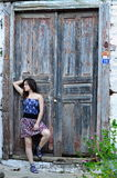 The girl standing on steps near an old door Royalty Free Stock Images