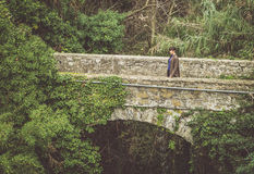 Girl standing on a stone bridge Royalty Free Stock Images