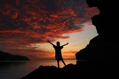 The girl standing and stretch the arms on the rocks near the bea. Ch with beautiful red sky sunset Stock Photo