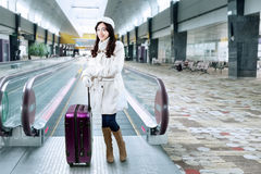 Girl standing with a suitcase in the airport hall Stock Photo