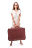 Girl standing with suitcase. Isolated on white Stock Photography