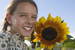 Girl (9-11) standing beside sunflower growing in garden, smiling, close-up, portrait Stock Photography