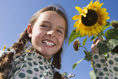 Girl (9-11) standing beside sunflower growing in garden, smiling, close-up, portrait, low angle view Royalty Free Stock Photo