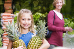 Girl (7-9) standing in supermarket, holding two pineapples, mother looking on in background, smiling, portrait Stock Photography