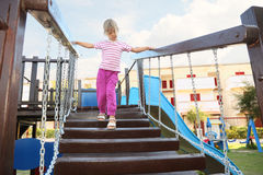 Girl standing on suspension bridge on playground Stock Image