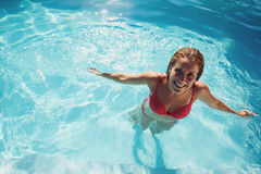 Girl standing in a swimming pool smiling Stock Photo