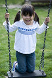 Girl standing on swing. Young girl standing on swing, smiling Stock Photo