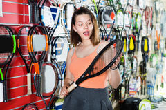 Girl standing in t-shirt in sporting goods store with racket Royalty Free Stock Photography