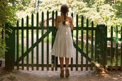 Girl standing on tiptoes and looking over the fence Royalty Free Stock Photography