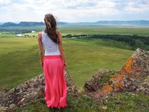 The girl is standing on the top of the mountain hand in the sides. Stock Photography