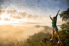 Girl standing on top of the mountain. With raised hands relaxing with nature royalty free stock image