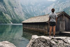 Girl standing on top of a rock and wooden cottage in beautiful l. Ake in the Alps with misty mood Royalty Free Stock Photo