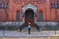 A girl standing toward a red brick building in autumn, in the center of Malmo, Sweden.  Royalty Free Stock Photos