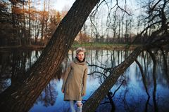 Girl standing on a tree near the pond in early spring. Blonde girl standing on a tree near the pond in early spring Stock Photo