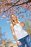 Girl standing under cherry tree in spring Royalty Free Stock Photos